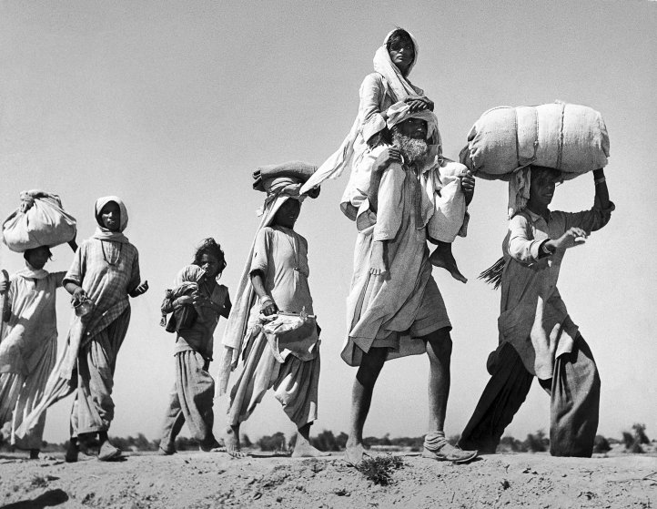 Sikh carrying his wife on his shoulders as he walks with others migrating to their new homeland after the creation of Sikh and Hindu section of Punjab India due to the division of India.